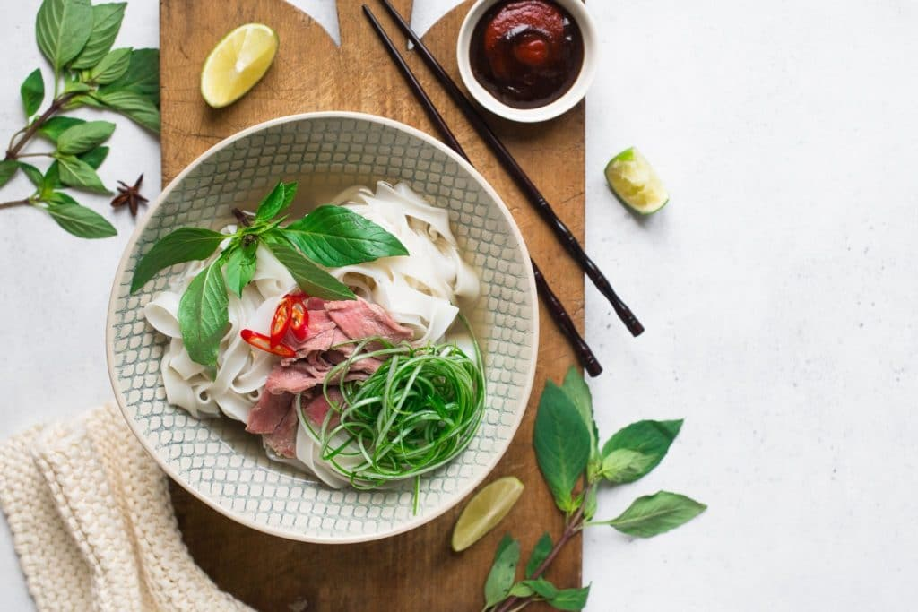 vietnamese beef pho in bowl on wooden chopping board