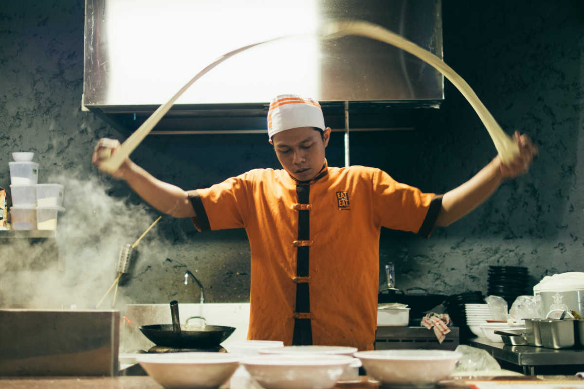 Chinese noodle maker stretching lo mein noodles