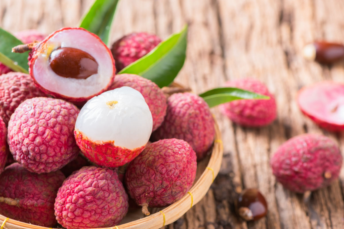 Bowl of fresh lychee fruits with one fruit partially pared back.
