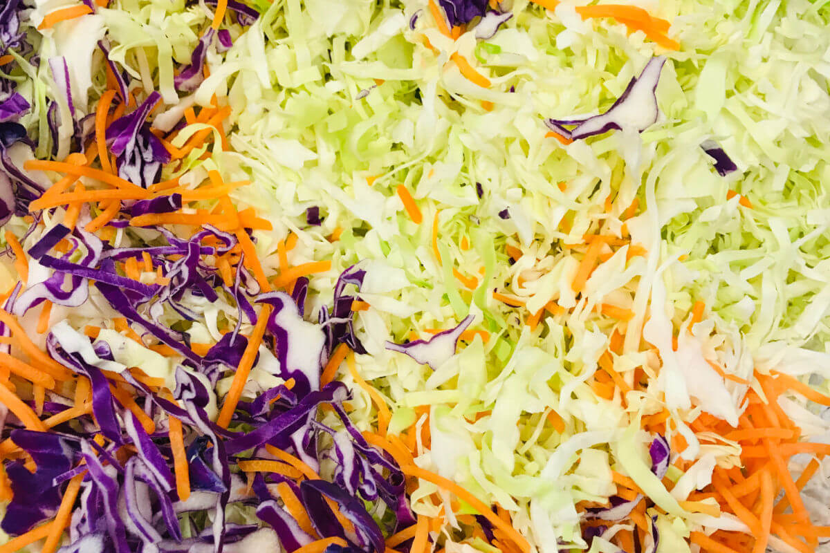 Bowl of shredded cabbage, carrots, pear, and cilantro to make Crunchy Asian Slaw.