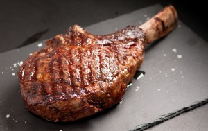 Perfectly grilled tomahawk steak on a slate board