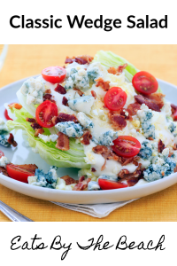 Wedge of iceberg lettuce with blue cheese dressing, halved cherry tomatoes, bacon, and crumbled blue cheese
