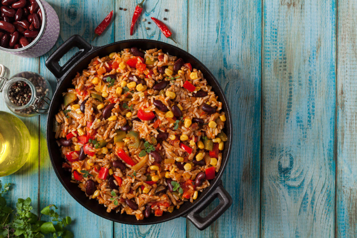 Cast iron skillet of Spicy Mexican Rice Pilaf - spicy rice, black beans, corn, and peppers in a savory chili sauce.