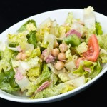 Chopped Italian salad on a white plate with a black background