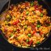 Chicken, chorizo and shrimp paella in a black pan