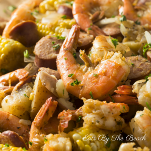 A spicy low country shrimp boil.  A pile of boiled shrimp, corn, potatoes, and smoked sausage served on brown paper.