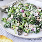 White plate with a creamy broccoli salad with red onion, raisins, and nuts