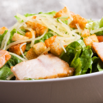 Gray bowl of caesar salad with homemade croutons, homemade caesar dressing, and sliced grilled chicken.