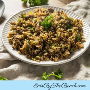 White plate of Cajun Dirty Rice with rice, ground beef, Italian sausage, onions, celery, green pepper, and spices.