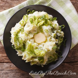 Bowl of the Irish side dish, Colcannon, which is mashed potatoes, steamed cabbage, scallions, and parsley. It is garnished with butter.