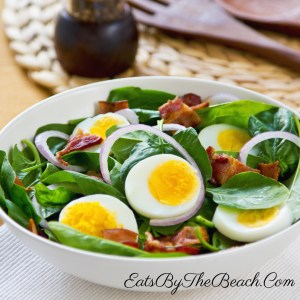 Bowl of fresh spinach salad with sliced hard boiled egg, thinly sliced red onion, crispy bacon crumbles and a sweet and sour bacon dressing. This is a simple salad recipe.