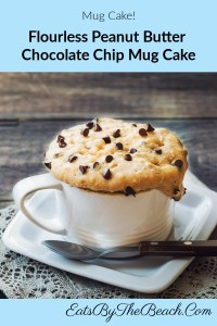 Microwaveable, flourless, peanut butter mug cake with chocolate chips in and sprinkled on top of the cake.