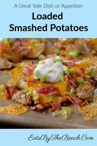 A plate with a baby potato that has been boiled, smashed into a patty and then browned in garlic butter. It's then baked with cheddar cheese and bacon, then garnished with sour cream and chopped green onion. This loaded smashed potato has all the flavors of your favorite loaded baked potato.