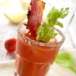 Tall glass of Barbecue Bloody Mary vodka cocktail with just a hint of barbecue sauce and garnished with barbecue seasoning, celery, and a crispy bacon strip. The perfect blend of tangy, savory, and a bit of sweetness.