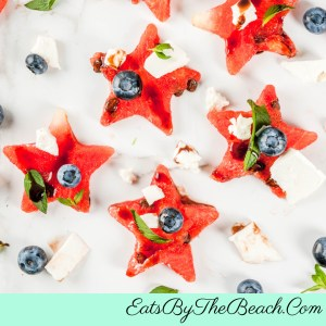 A platter of Balsamic Fruit Salad consisting of star shaped watermelon slices, fresh blueberries, feta cheese, and drizzled with balsamic glaze and fresh mint. A great 4th of July side dish.