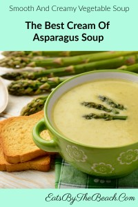 Bowl of smooth and creamy Cream Of Asparagus Soup, garnished with the tops of the asparagus.