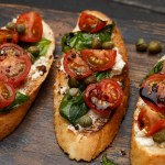 A plate of Goat Cheese Caprese Bruschetta - garlic toasts, spread with creamy goat cheese, and topped with a cherry tomato and balsamic salad, then garnished with capers, basil leaves, and salt & pepper.