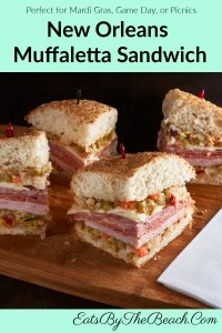 A wedge of New Orleans Muffaletta sandwich with homemade olive salad and layers of Italian meats and cheeses. It's a staple for Mardi Gras, tailgating parties, or a weekend picnic.
