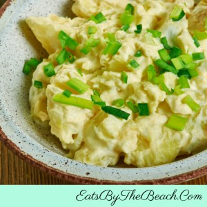Bowl of creamy, tangy Southern Potato Salad garnished with sliced scallions.