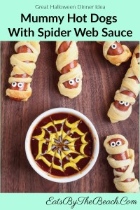 Mummy Hot Dogs With Spider Web Sauce - Crescent dough wrapped around a hot dog like a mummy and baked, then garnished with candy eyes and served with a bowl of ketchup with a yellow mustard 'spider web' drawn on top.
