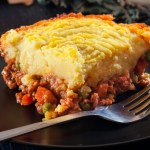 A casserole dish of comforting Shepherd's Pie - ground beef and veggies in a rich gravy and topped with a smooth, cheesy, creamy mashed potato topping.