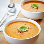 A hot, steaming bowl of creamy Easy Butternut Squash Soup garnished with cracked red and black pepper and a fresh basil leaf.
