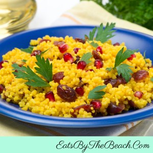 Curried Couscous with jeweled fruit - couscous spiced with curry powder, sauteed onions, garlic, raisins, and fresh pomegranate seeds.