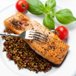 Plate of healthy pan roasted salmon over a bed of French green lentil salad.