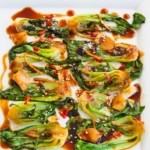White platter with stir-fried Spicy Garlic Bok Choy in an Asian inspired sauce with garlic, red Thai chiles, and sesame seeds as a garnish.