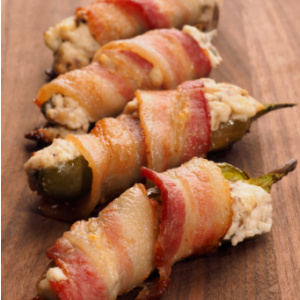 A plate of Extra Flavorful Jalapeno Poppers - jalapenos stuffed with cream cheese and cheddar, then wrapped in bacon. It's a great game day snack.