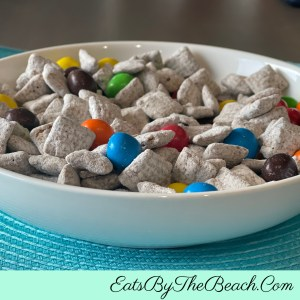 Bowl of Peanut Butter Puppy Chow - Rice cereal coated in chocolate and peanut butter and dusted in powdered sugar then mixed with peanut butter M&Ms for a dessert that both children and adults will love.
