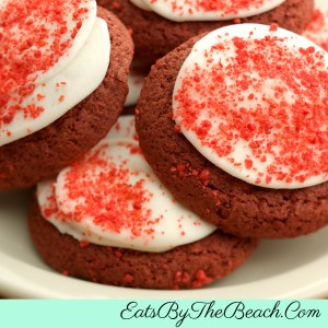A plate of homemade, Soft Red velvet Cookies With Cream Cheese Frosting and sprikled with red velvet cookie crumbs.