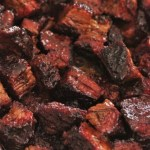 A pan of Burnt Ends aka: Meat Candy - cubes of tender brisket that's glazed with barbecue sauce until the cubes are sticky with crunchy caramelized edges.