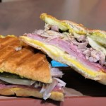 Tampa Cubano Sandwich - a pressed sandwich with mojo pulled pork, honey ham, Genoa salami, Swiss cheese, pickles, and yellow mustard on Cuban bread.