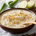 Bowl of steaming White Chicken Chili-full of chunks of chicken, white beans, green chiles,and creamy broth.