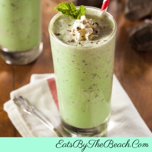 Glass of boozy Irish mint shake garnished with whipped cream and a sprinkle of chocolate
