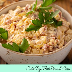 Bowl of Game Day Reuben Dip - corned beef, sauerkraut, and cheese with rye toasts for dipping