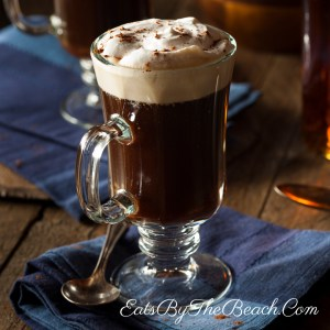 Amug of steaming Irish Coffee garnished with whipped cream and a sprinkle of grated chocolate