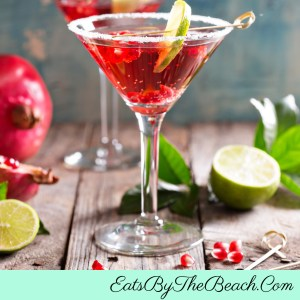 A crimson colored Pomegranate Martini - made with Mandarin vodka, orange liqueur, pomegranate juice, and orange blossom water. It's garnished with a lime slice and pomegranate seeds.