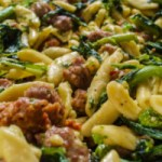 Bowl of tender cavatelli with sausage and broccoli rabe, garnished with a dollop of ricotta cheese and a sprinkle of parmesan.