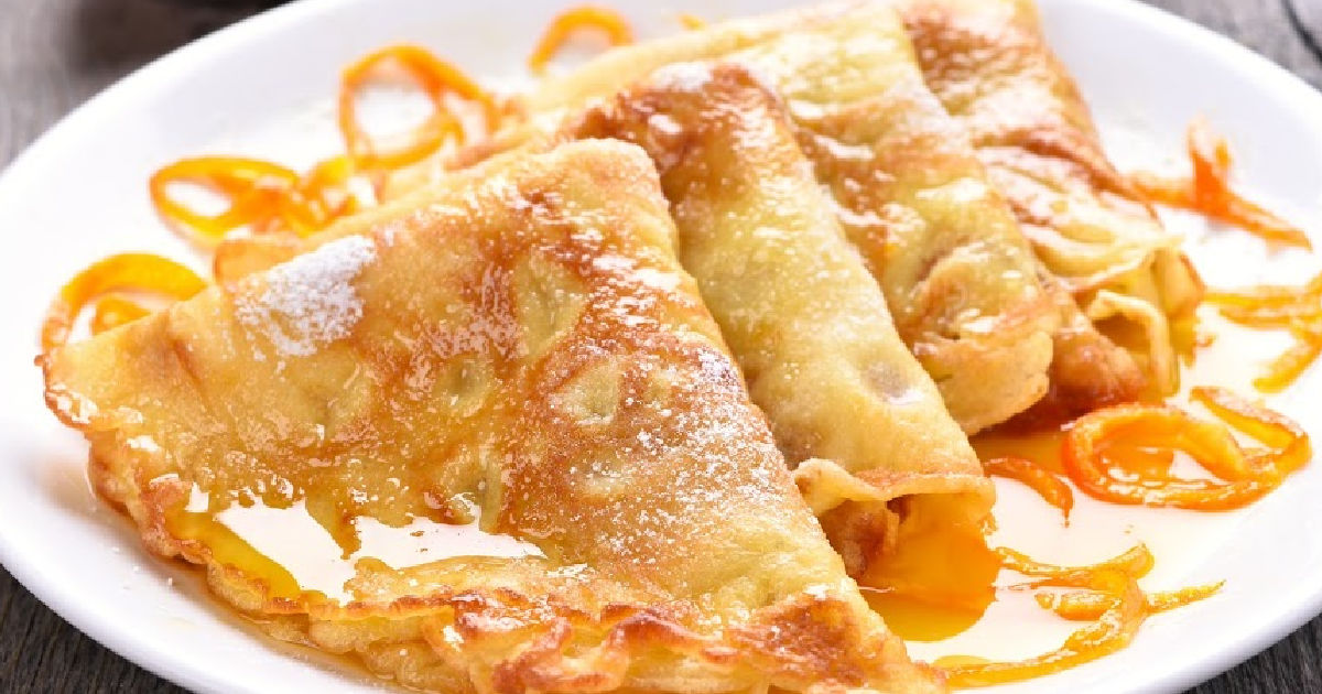 A plate of Crepes Suzette with orange sauce and garnish of orange zest