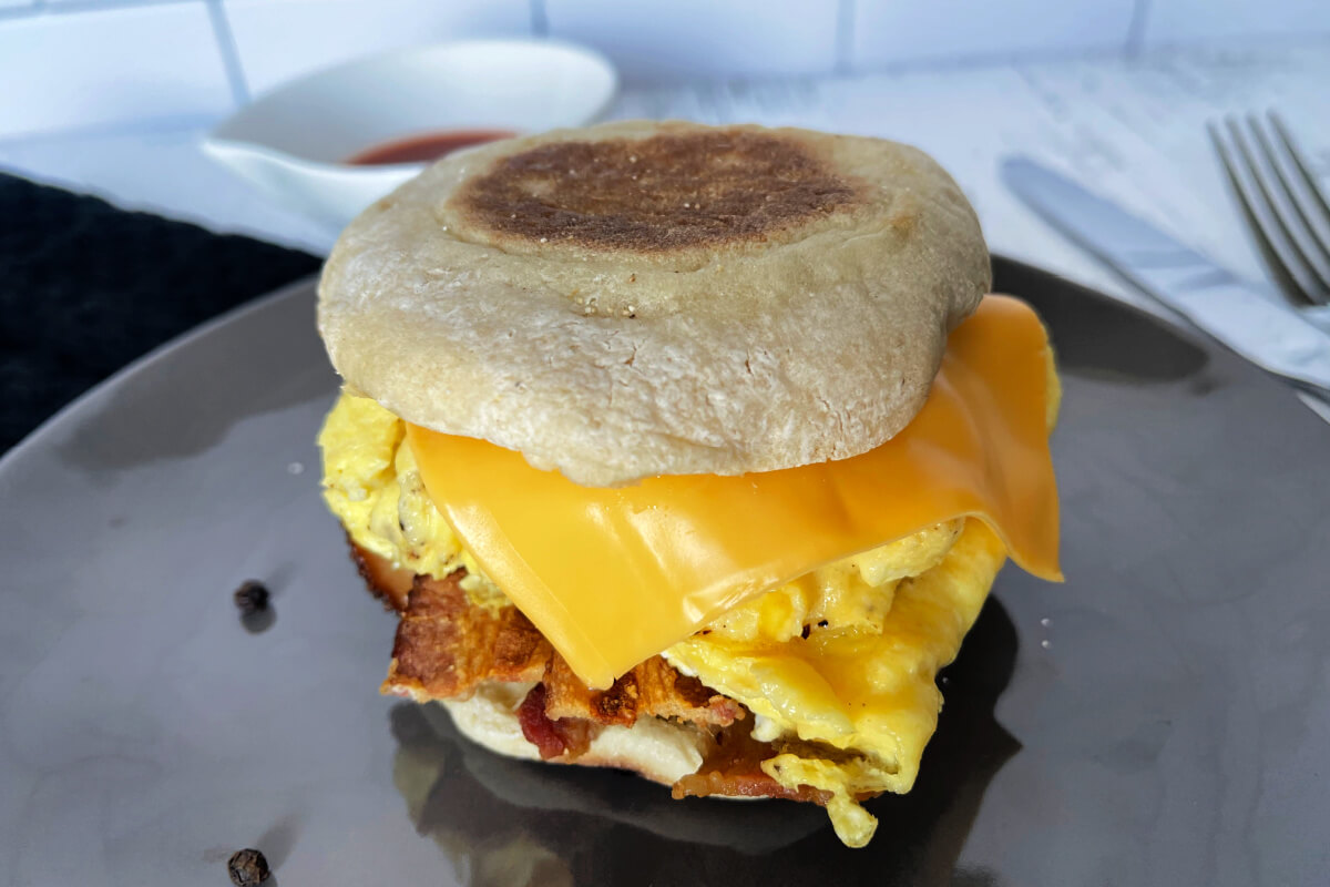 Bodega Style Egg Sandwich - toasted, buttered English muffin with a soft scrambled egg, crispy bacon, and melted cheese - a unique New York City breakfast