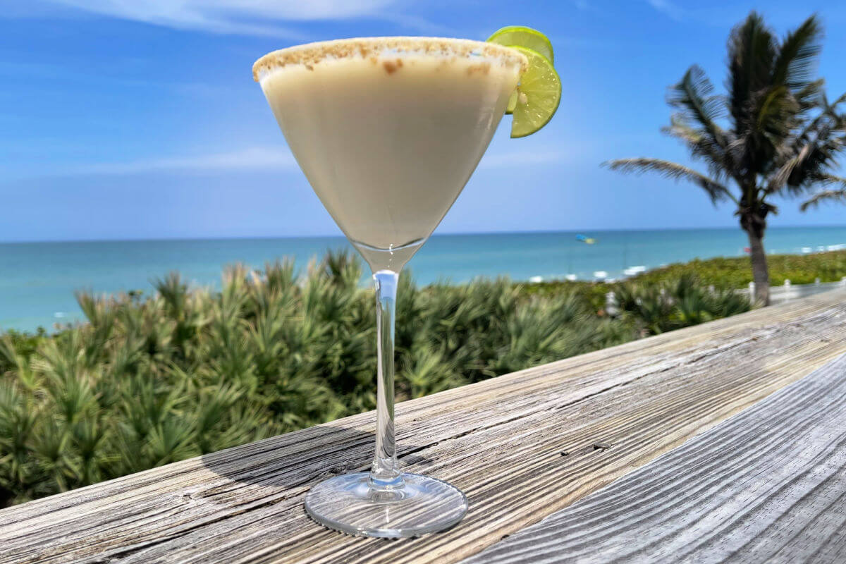 A sweet, creamy Key Lime Pie Martini on a wooden table by the beach.