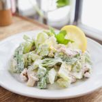 Plate of Classic Waldorf Salad-chopped apples, celery, walnuts, romaine lettuce, and grapes in a creamy yogurt dressing