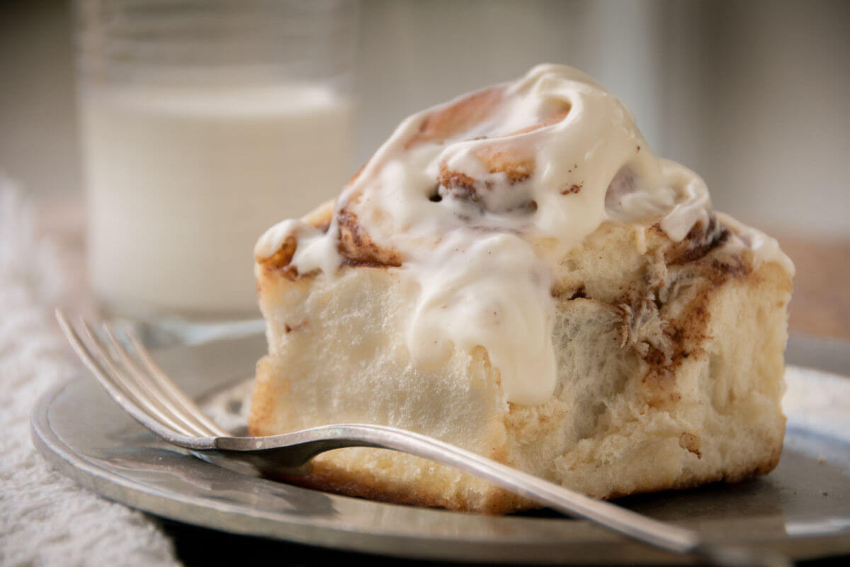 Homemade, easy cinnamon roll on a gray plate, with a fork.