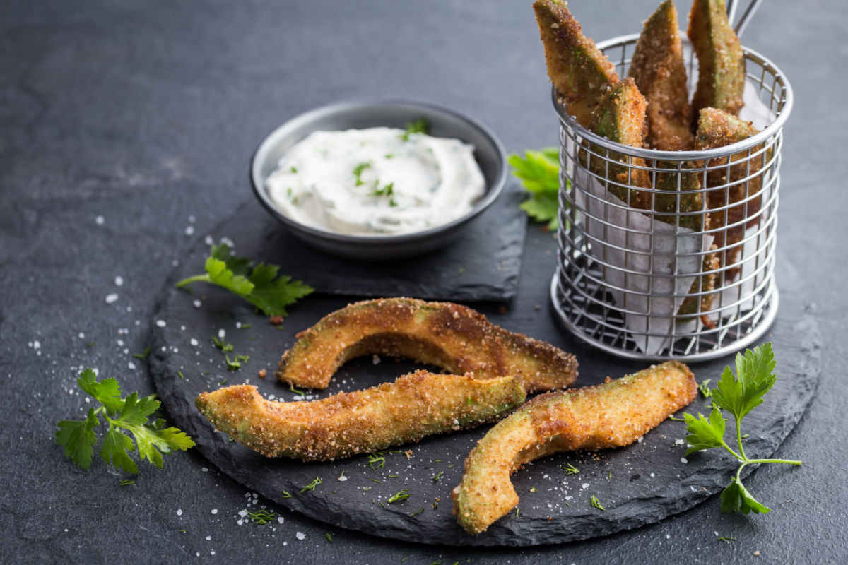 Slate plate of crispy avocado fingers served with a spicy lime crema - slices of avocado are breaded and pan fried and served with a sour cream, cayenne, and lime.