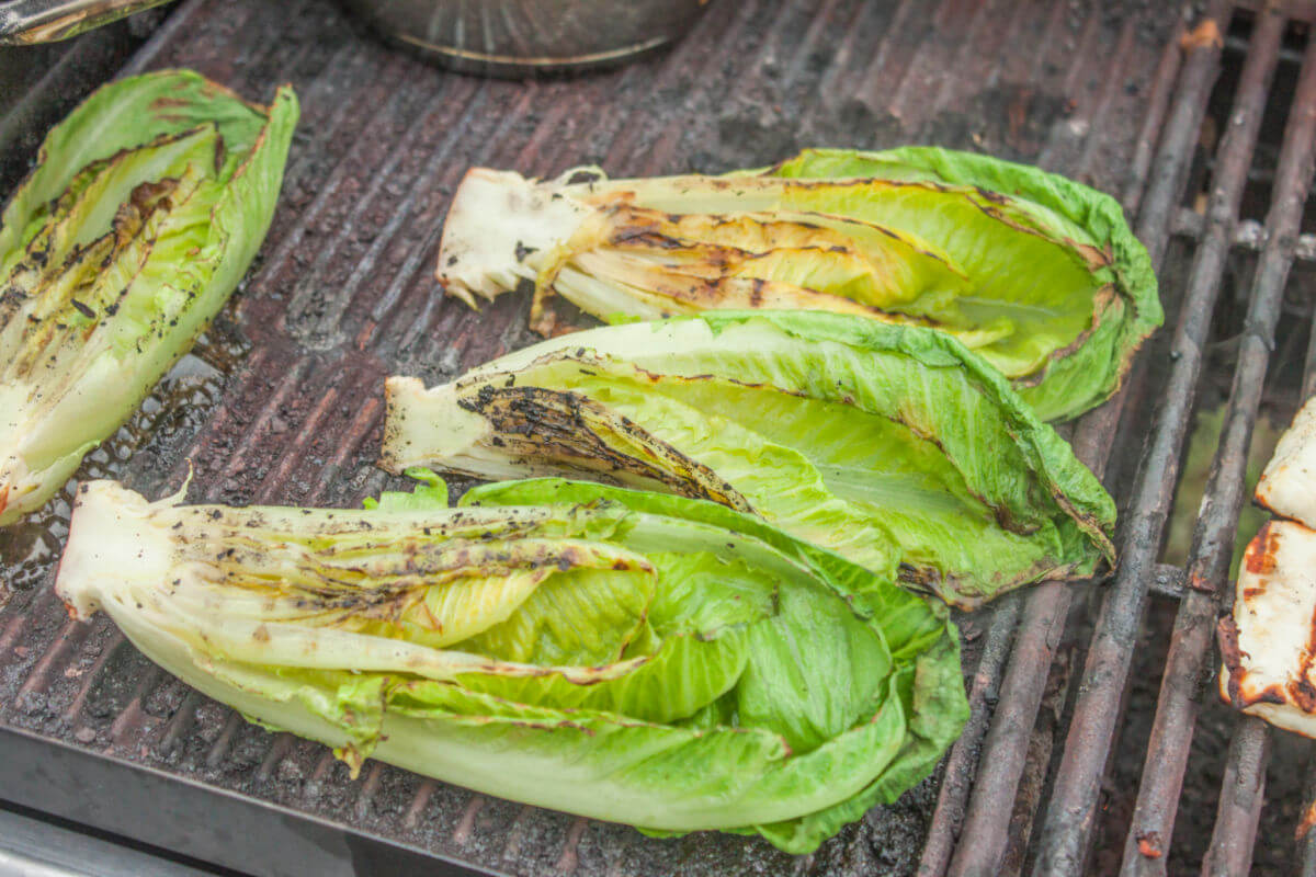 Heads of romaine lettuce on the grill to make Grilled Romaine Salad