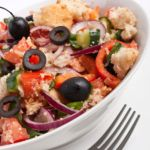 Bowl of panzanella salad - Italian bread, onions, tomatoes, black olives, and basil in a homemade Italian dressing