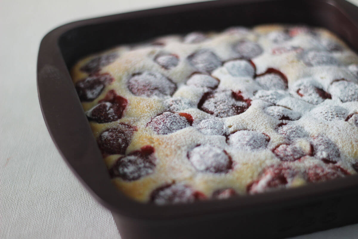 Pan of Fresh Strawberry Clafoutis with fresh berries baked in an almond-scented custard.