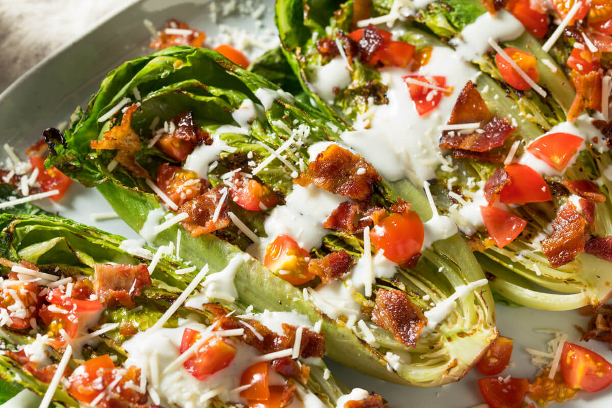 A platter of Grilled Romaine Salad with grilled romaine lettuce, crispy bacon, fresh tomatoes, Parmesan cheese, and a homemade, creamy dressing.